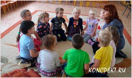 Дети с психологом проводят занятие на ковре
