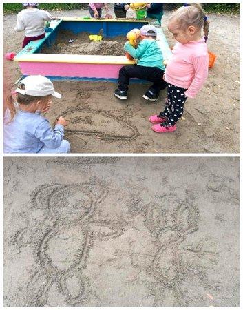 Дети рисуют на песке